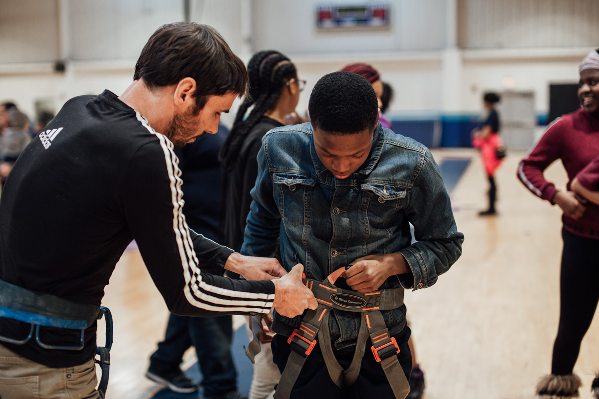 Kevin Jorgeson helps a boys and girls club member with his harness