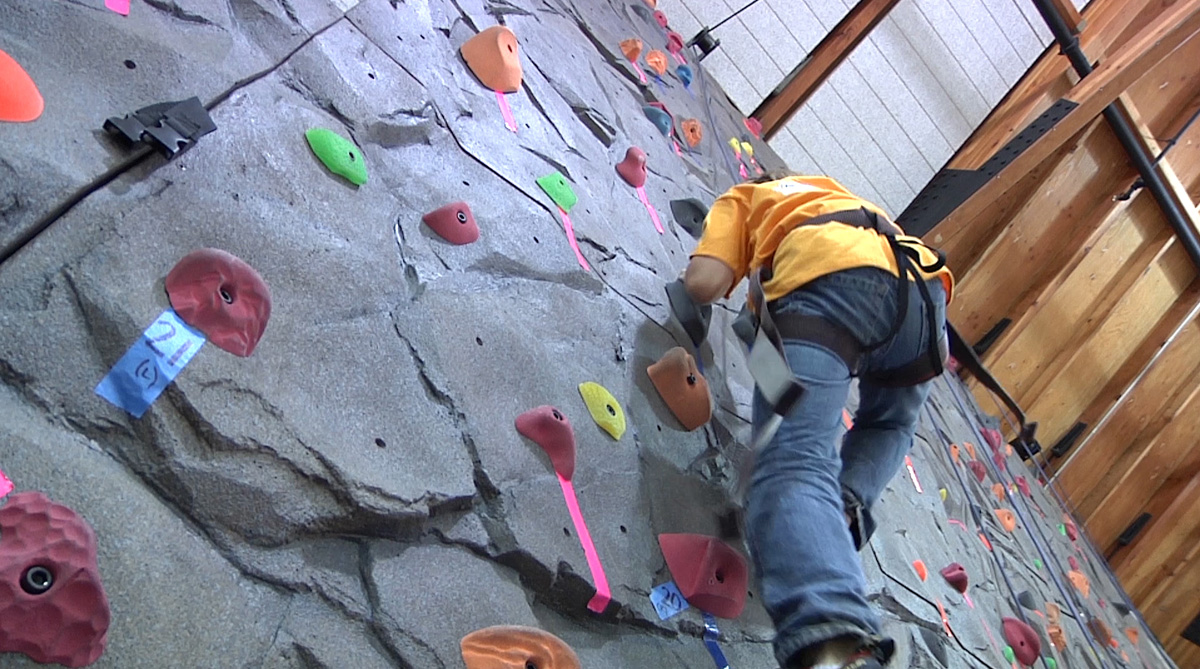 A Boys and Girls Club member tries climbing for the first time.