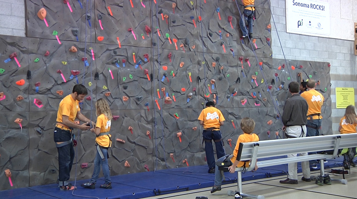 Kevin Jorgeson helps a Boys and Girls Club member with her harness.