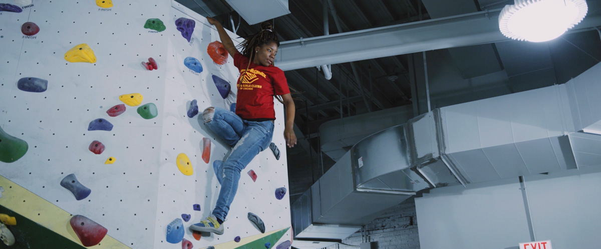 A Chicago Boys and Girls Club member gets to the top off the wall at First Ascent in Chicago.