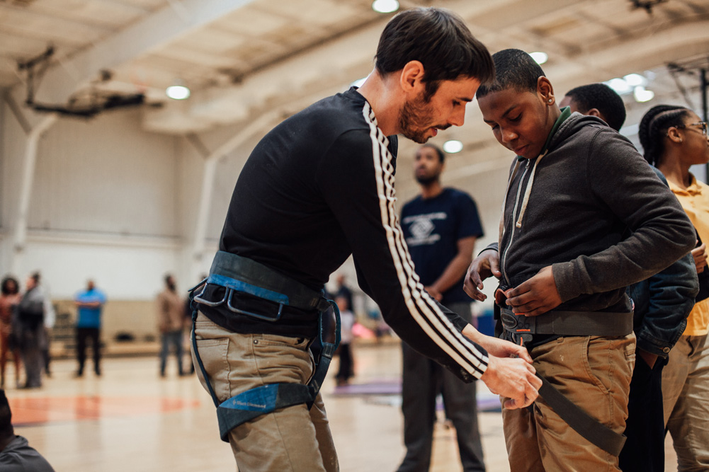 Kevin helps fit a climbing harness on a Boys and Girls club member.