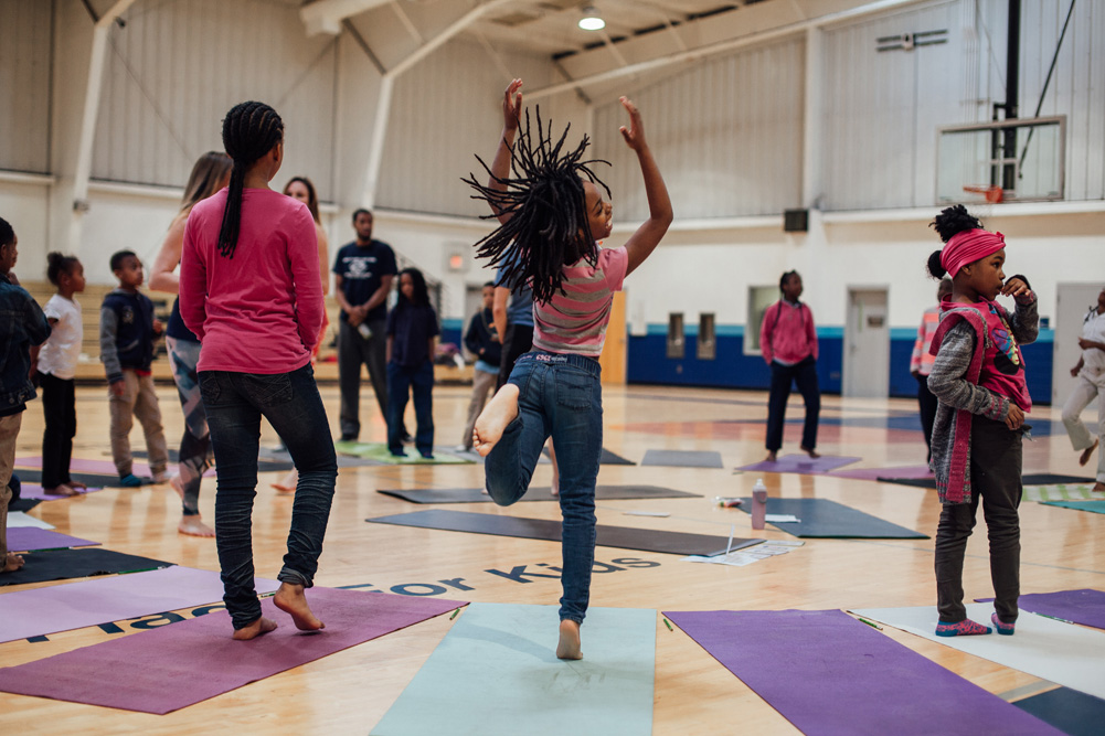 Saint Louis Boys and Girls club members try yoga before the opening of the wall.