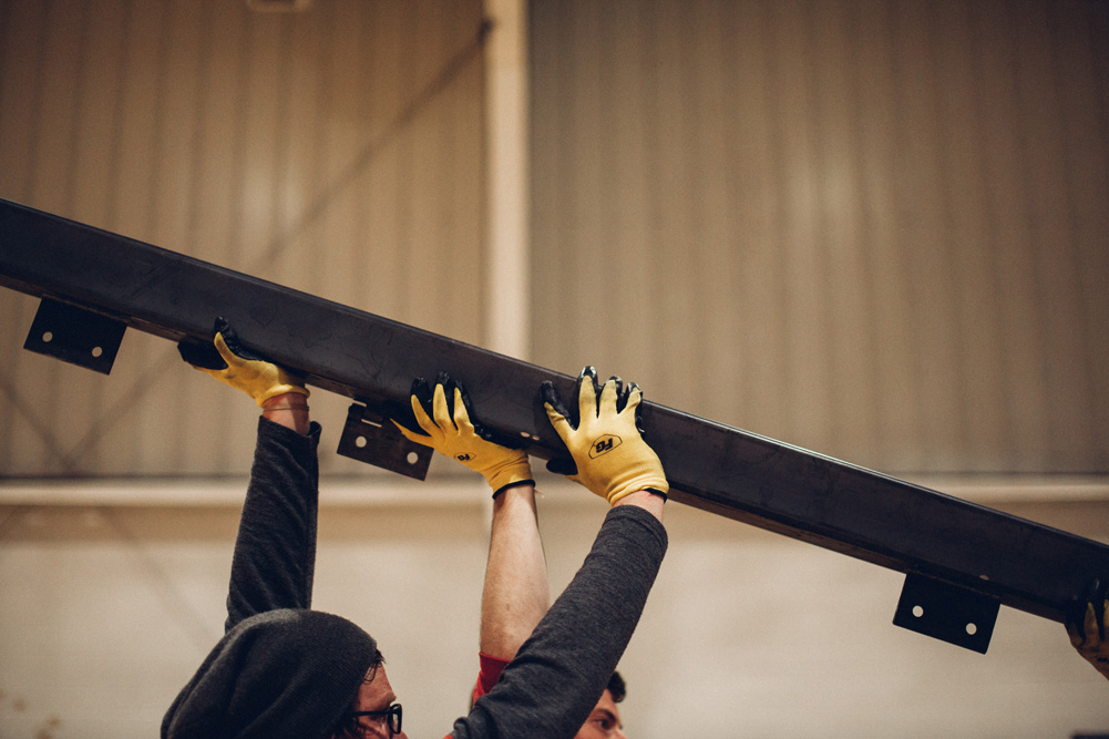 An ElDorado team member helps lift an iron beam.