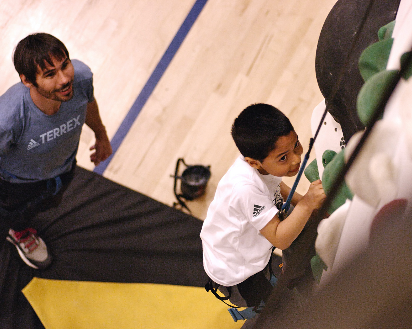 Kevin Jorgeson watches as a boys and girls club member climbs a new 1Climb wall for the first time.