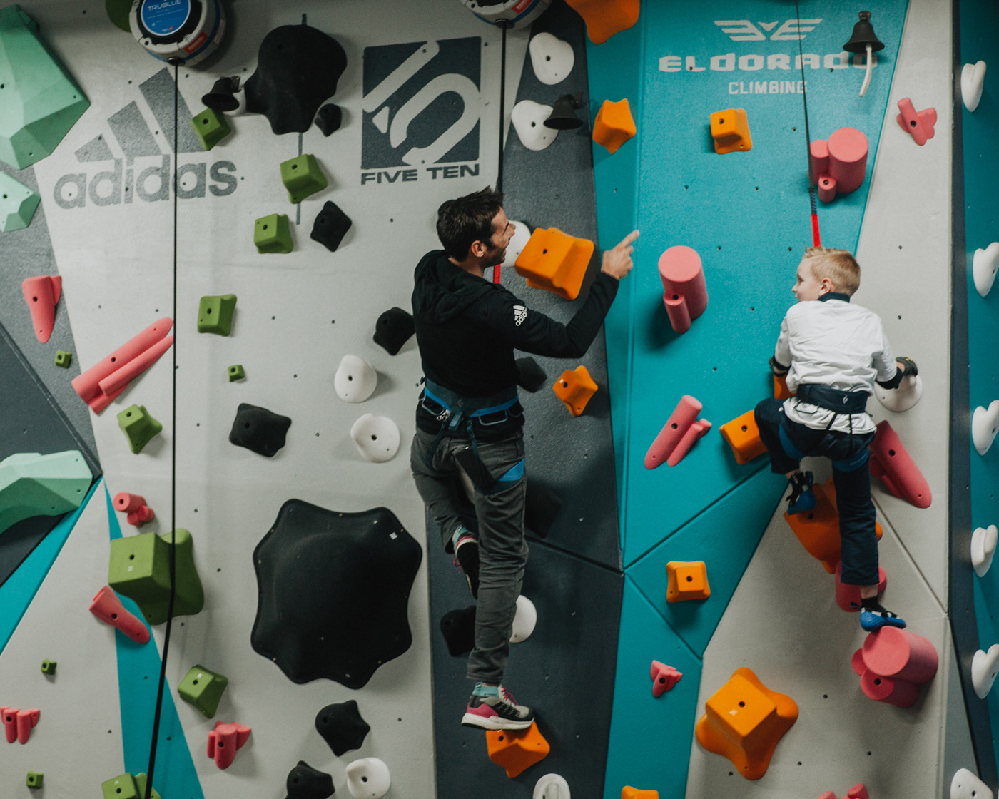 Kevin Jorgeson climbs on the 1climb wall with a boys and girls club member in santa rosa