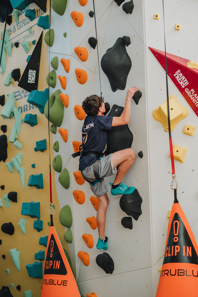 A Boys and Girls Club member climbs up a difficult climbing route