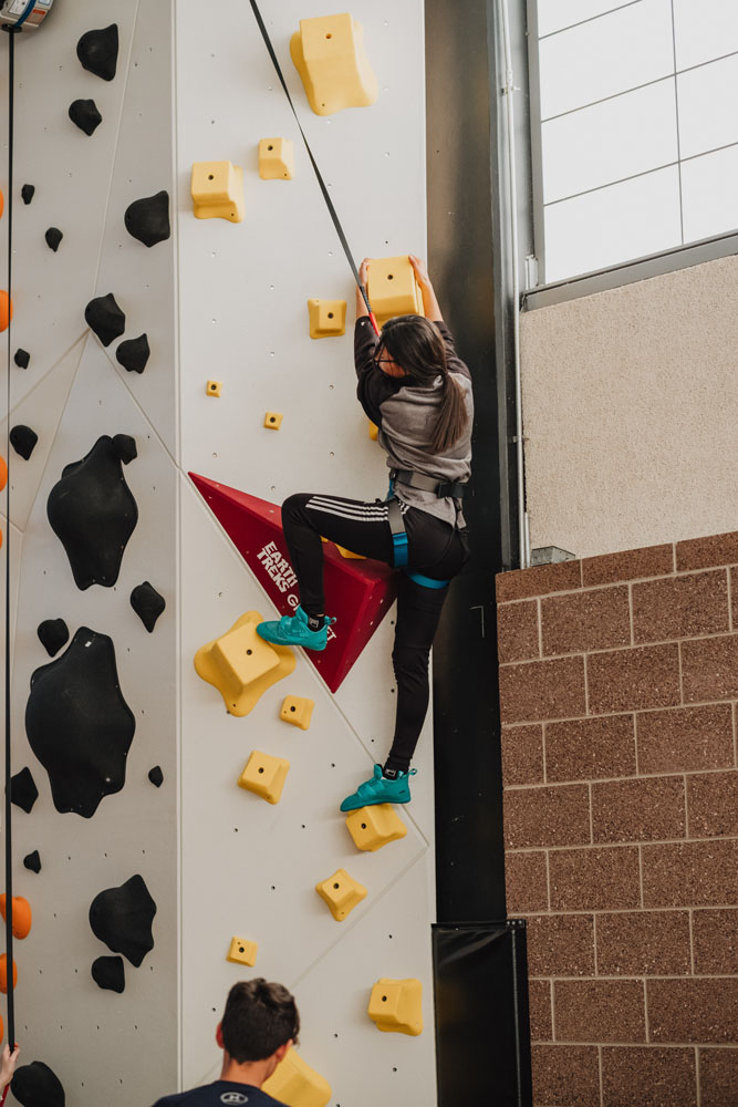 A Boys and Girls Club member climbs up a SO iLL climbing holds Wrecktangles route