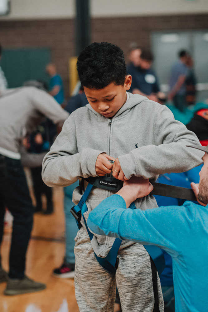 A Boys and Girls Club member tries on a climbing harness