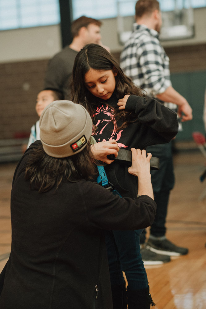 A boys and girls club member gets help with their climbing harness