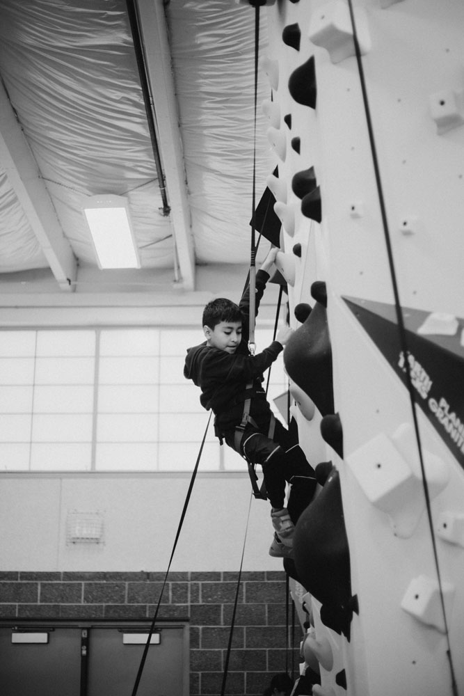A Boys and Girls Club member climbs for the first time on the newly constructed 1Climb wall