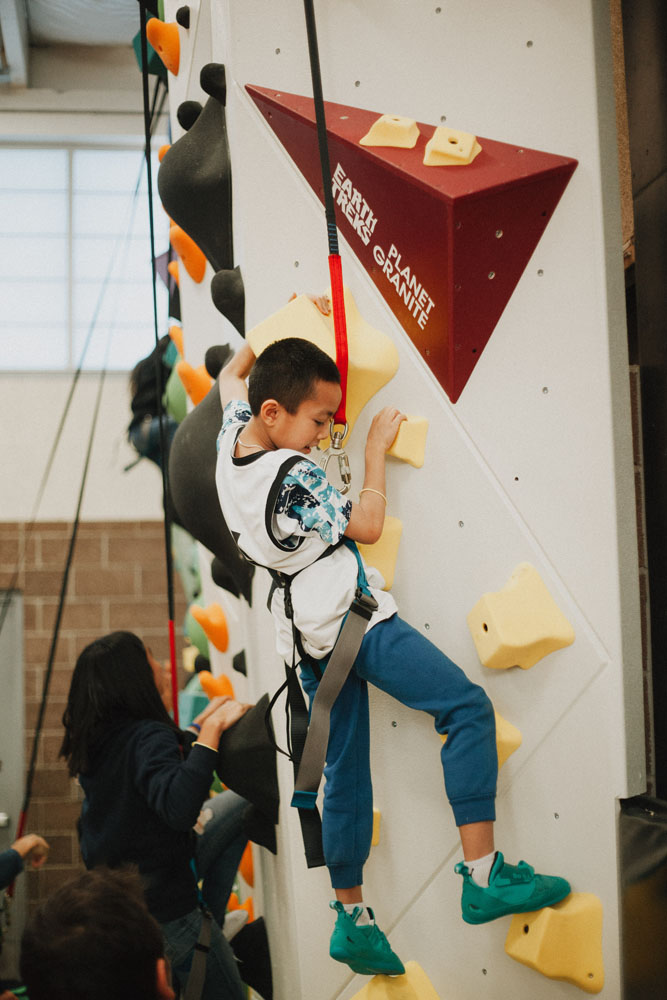 A Boys and Girls Club member climbs on the So iLL Wrecktangles climbing holds