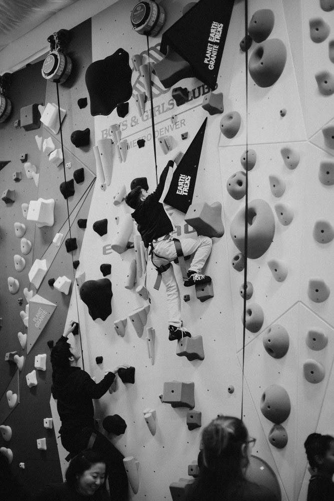 A Boys and Girls Club member climbs on a Volume hold