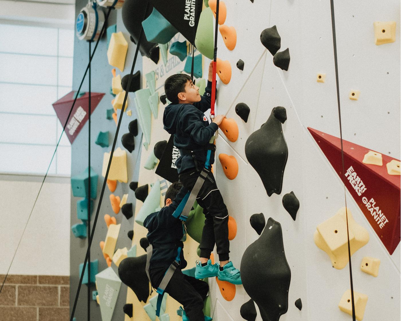 A boys and girls club member climbing up the new Denver 1Climb wall